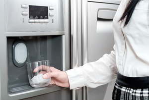 A woman uses a water dispenser in a fridge.