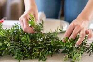 hands assembling a green garland