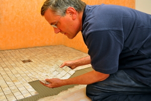 Man repairing a sheet of mosaic ceramic tiles on a shower floor.