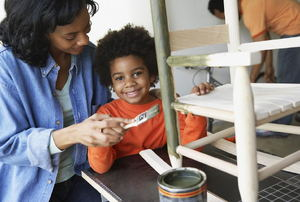 A mom and son painting a wood rocking chair.