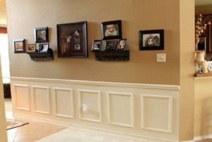 hallway with wainscoting and pictures on a wall