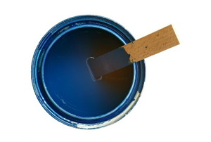 A paint can of medium blue paint with a wood stir stick inside.