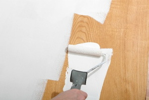 Using a paint roller to paint over wood paneling.