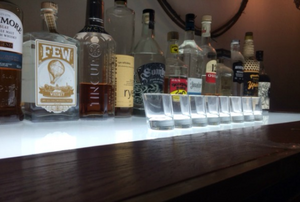 A row of shot glasses with a row of bottles behind them.