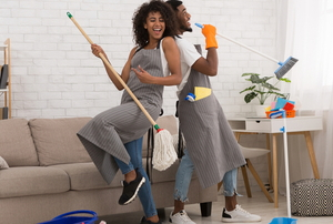 woman and man having fun with their spring cleaning tools