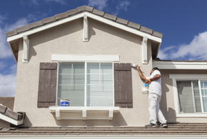 A man painting a outdoor windows and trim