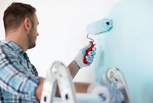 A man paints a room being painted light blue.