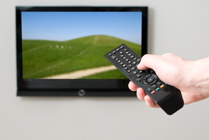 Pushing buttons on a remote aimed at a TV
