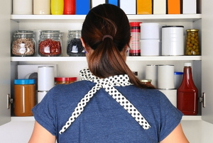 A woman looks at a pantry.