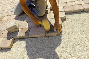 person installing tan brick pavers