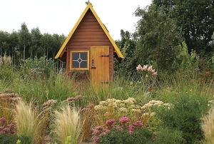 Playhouse in a yard with wild flowers.
