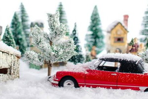 A winter scene of snow and small toys including a red car.