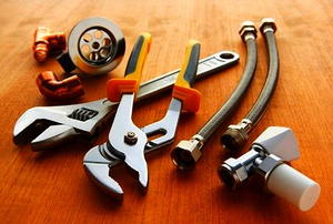 Plumbing tools and materials on wooden floor.