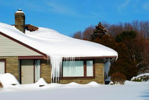 A house with snow-covered roof and ice hanging from gutters.