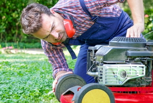 man checking broken lawn mower