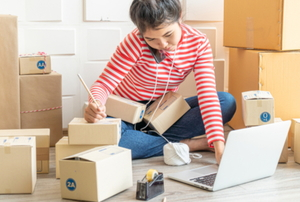 woman on a phone with a laptop surrounded by boxes
