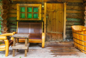 tiny cabin with wooden deck and furniture outside