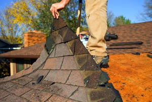 A worker lifting up a layer of shingles on a roof.