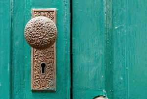antique doorknob on a green door