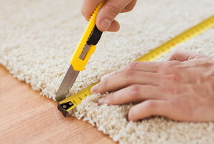 hands measuring and cutting carpet