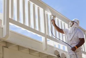 A painter using an electric spray painter to cover a deck railing.