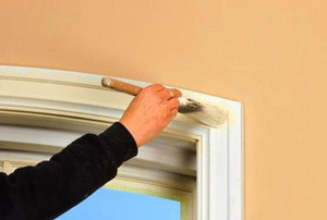 A painter working on trim in a doorway.