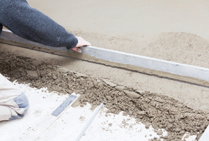 A screed being used on concrete.