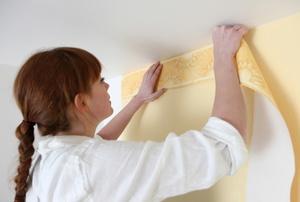 A woman installs wallpaper trim.