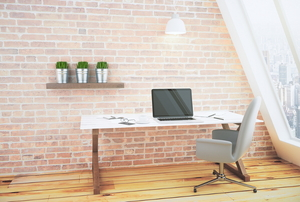 Office space next to a window and brick wall