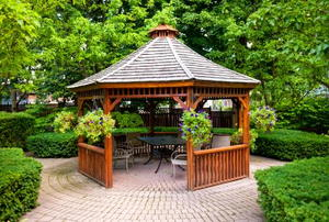 A pergola in landscaped garden with an interlocking paver patio.