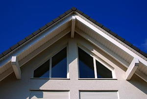 Exterior view of attic-gable windows on a white house with a pitched roof.