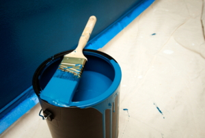 A paintbrush dipped in blue paint sits across the top of a blue paint can.
