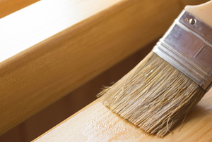 paintbrush applying clear finish to wood