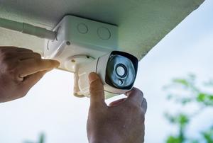 hands installing security camera