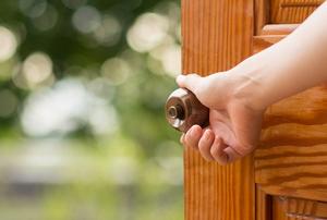 A woman opens a door.