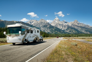 RV driving down a road next to mountains