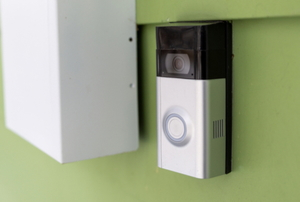 doorbell with camera on green wall