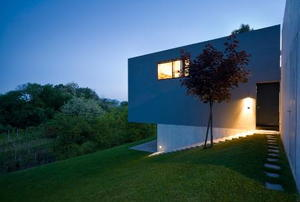 A modern house sits on a hill in twilight.