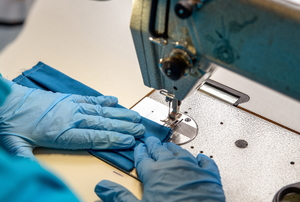 Person with gloves sewing