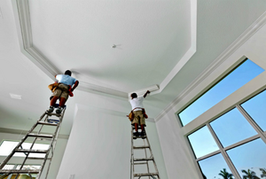 Two people paint cathedral ceiling.