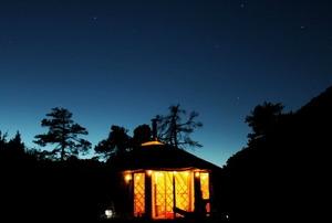 A lit yurt against a nighttime sky.