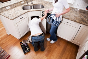A couple of DIYers working on a plumbing problem in the kitchen.