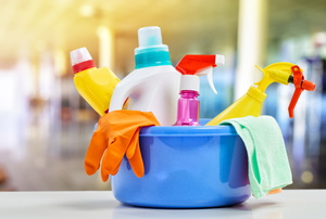 Colorful cleaning supplies in a bucket.