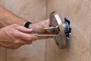 A man repairs a shower faucet.