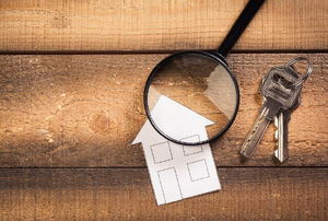 A paper house with a magnifying glass and keys next to it.
