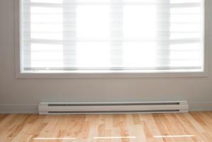 A singular baseboard heater installed below the window in a bedroom.