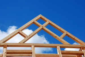A wooden roof truss secured to a wooden housing frame.