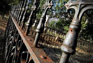 Old, weathered, ornate metal fencing