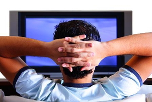 A view from behind a man watching television with his hands behind his head.