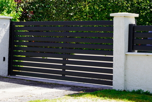 dark colored aluminum driveway gate between white pillars